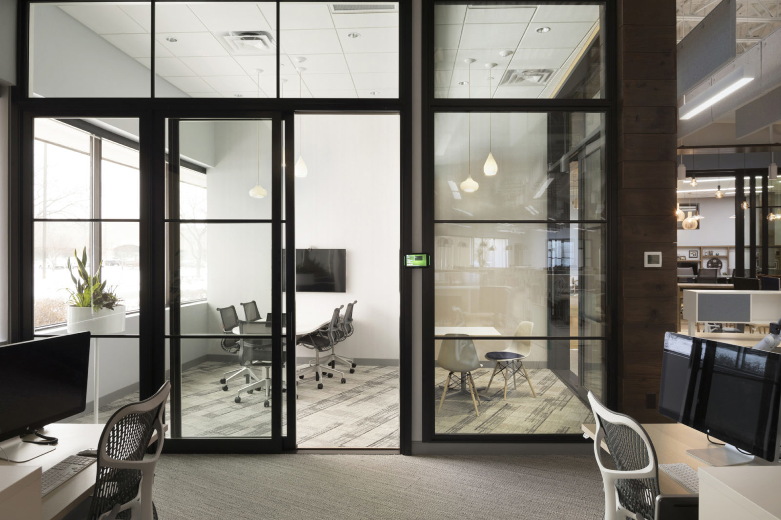Side by side conference rooms with video conference technology