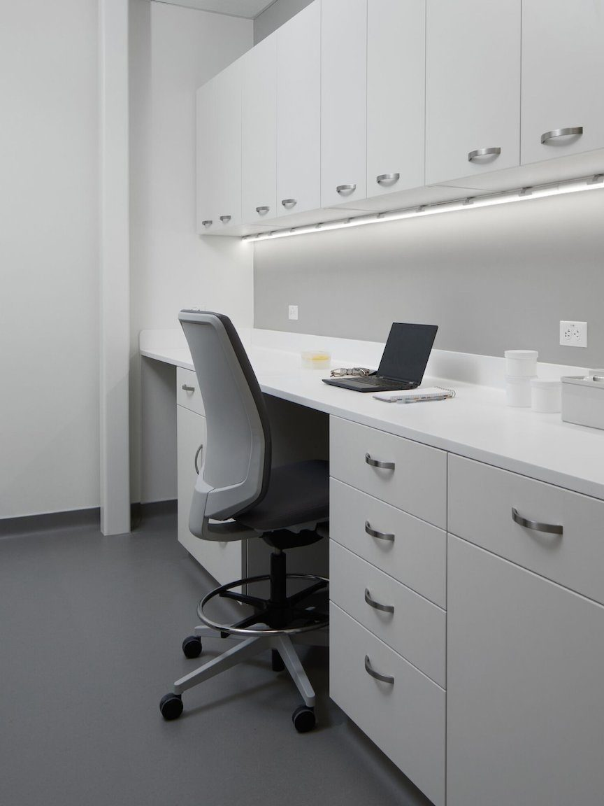 Laboratory workspace with white Mora casework for upper and lower cabinets and a Verus stool in a gray upholstery.
