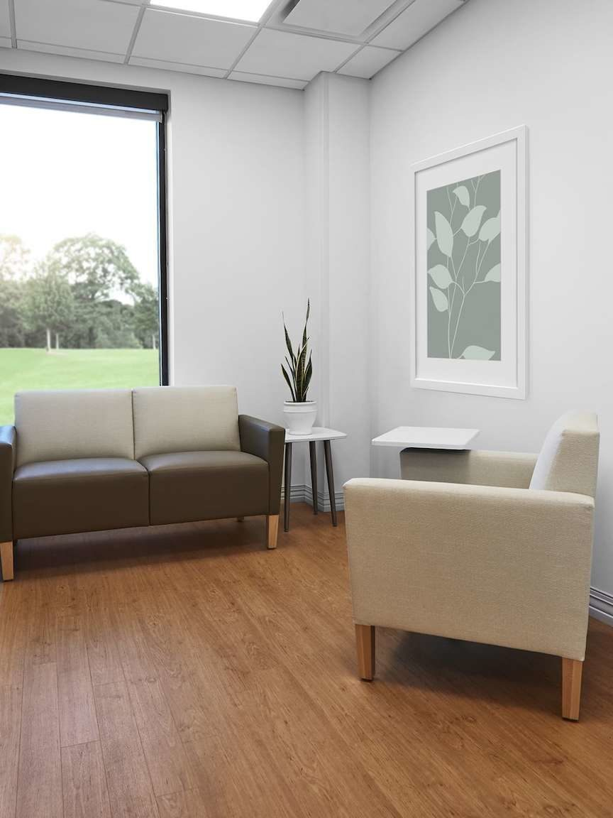 Patient consultation room with beige Nemschoff arm chair, Brown Brava Classic Multiple Seating, Nemschoff Palisade Mobile Table and Palisade Side Table.